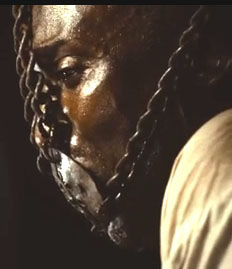 An African man wearaing an iron face mask chained around his head